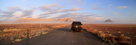 Foggy early morning on a dirt road, East of the Capitol Reef National Park, with Factory Butte in the distance